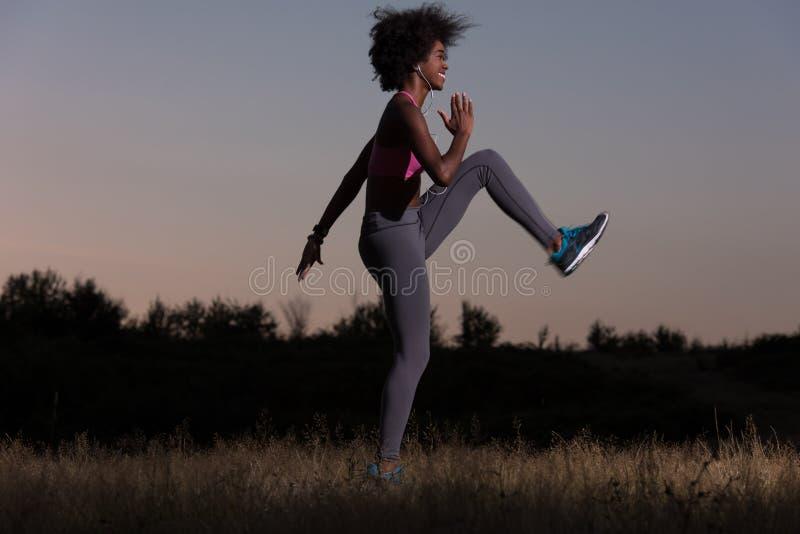 黑人妇女做着舒展锻炼放松和准备 库存图片