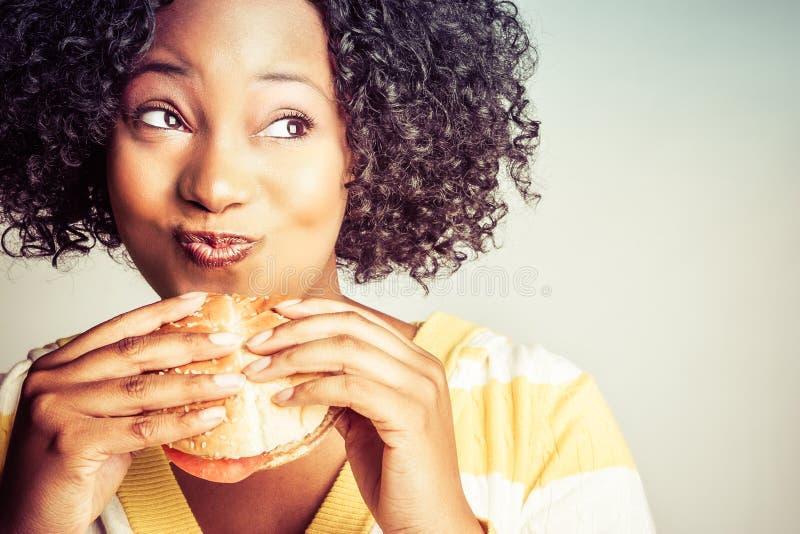 黑人妇女吃 库存照片