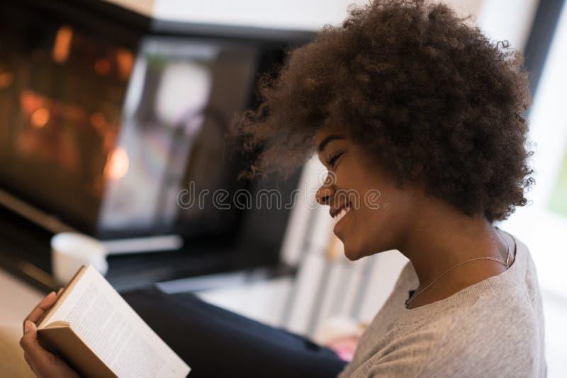 黑人妇女在壁炉前面的阅读书 图库摄影