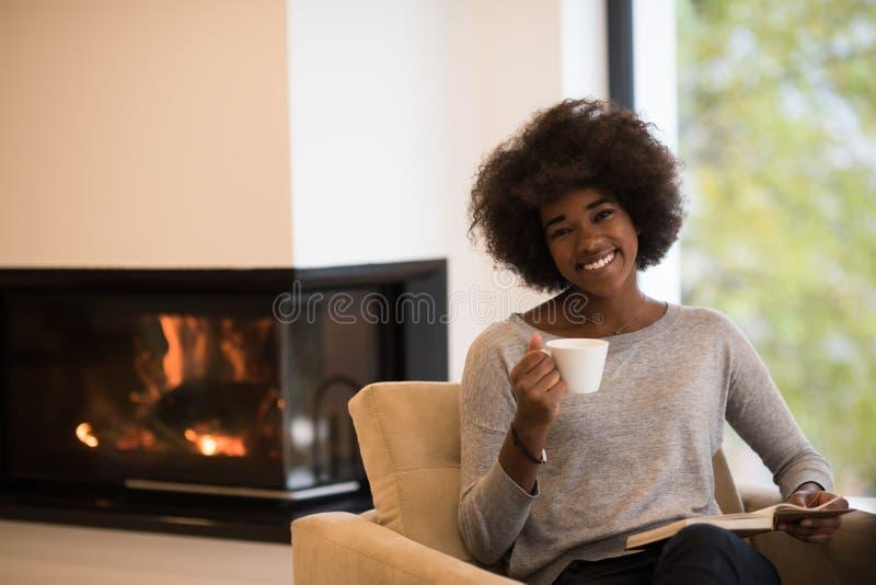 黑人妇女在壁炉前面的阅读书 免版税库存照片