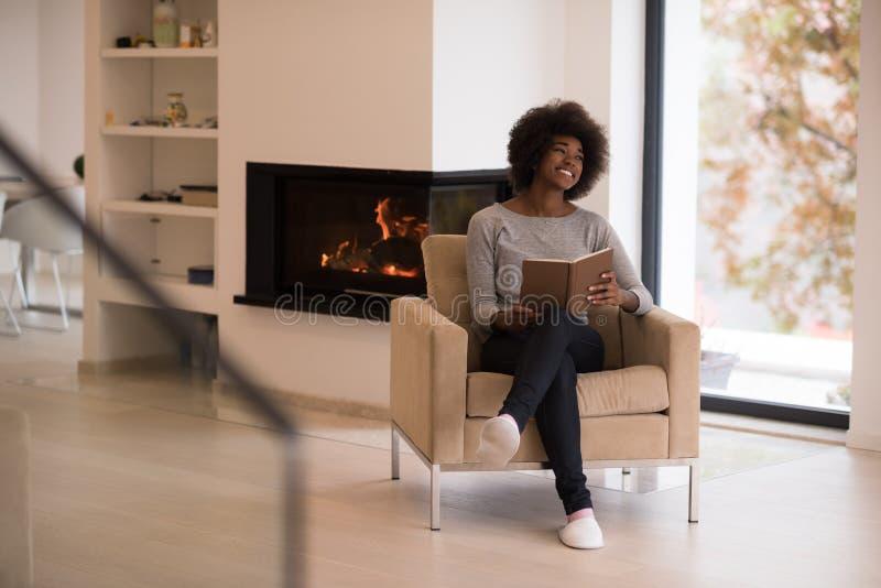 黑人妇女在家阅读书 图库摄影