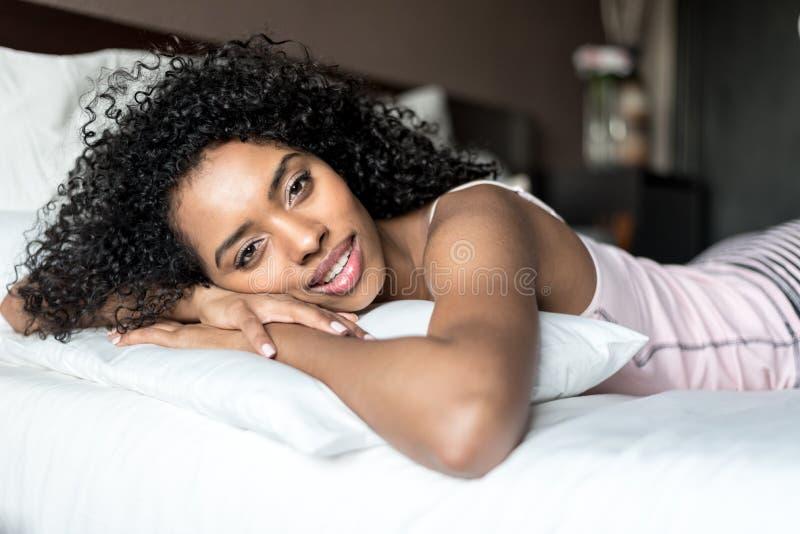 黑人妇女愉快在舒展的床上微笑和看camer 库存照片