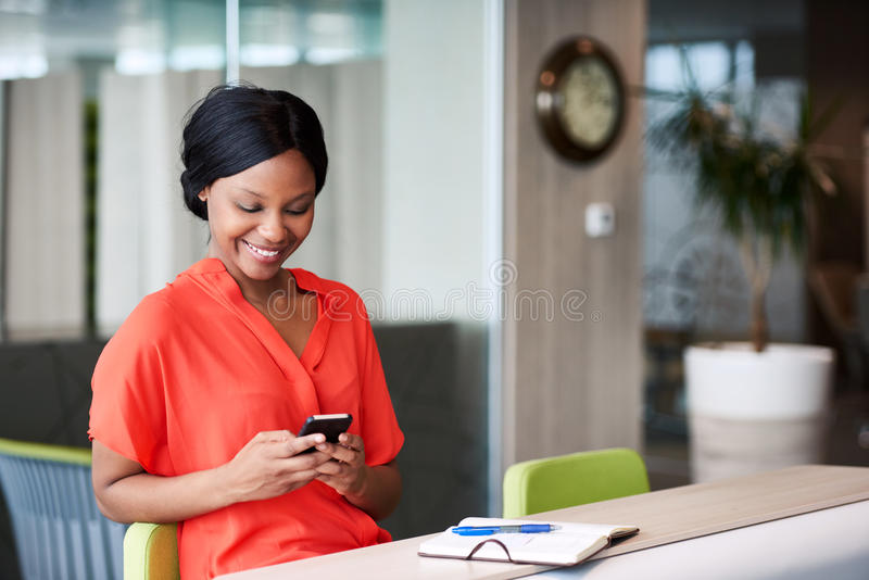 黑人妇女文字在她的手机的正文消息在家 库存照片