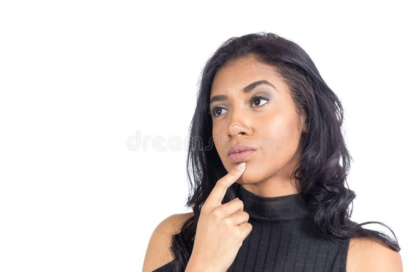 黑人妇女是与她的在她的下巴和认为的手指什么 免版税库存图片