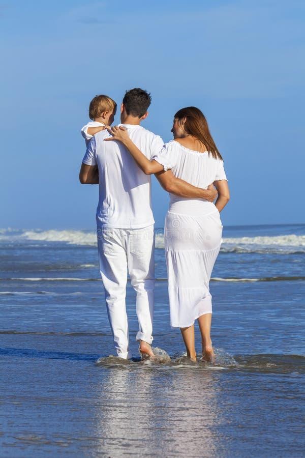 人妇女走在海滩的儿童家庭 免版税库存图片
