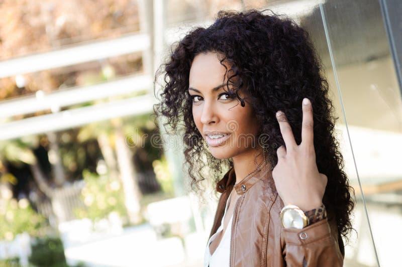 年轻黑人妇女,非洲的发型,在都市背景中 免版税图库摄影