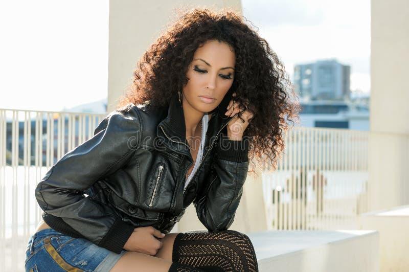年轻黑人妇女,非洲的发型,在都市背景中 免版税库存图片