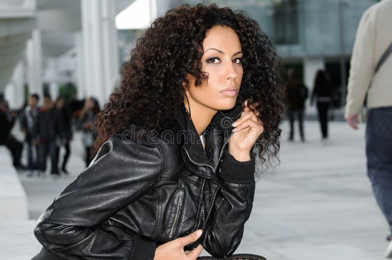 年轻黑人妇女,非洲的发型,在都市背景中 免版税库存照片