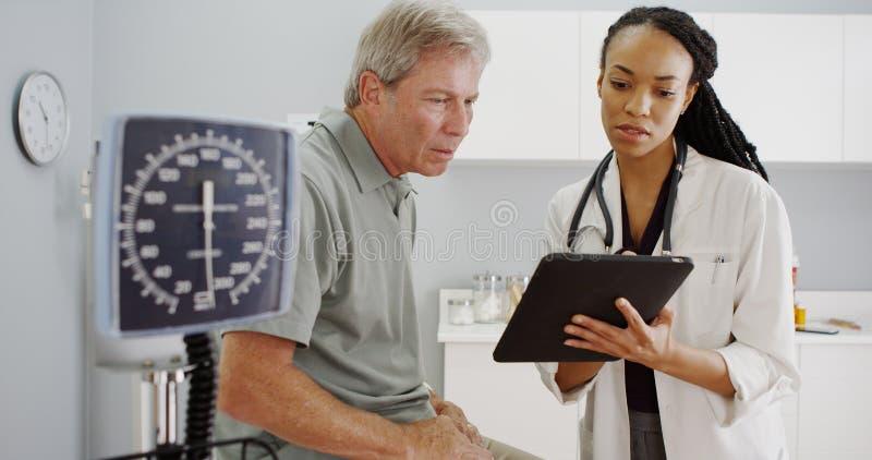 黑人妇女医生谈话与资深患者在办公室 免版税库存照片