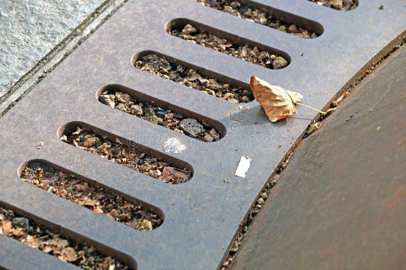 人孔盖金属,在街道的土气方形的流失,钢格栅下水道或 库存照片