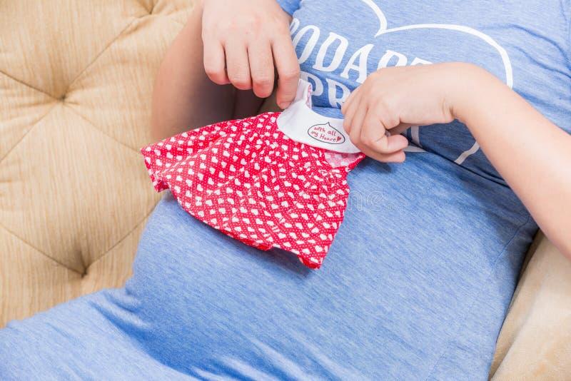 年轻人孕妇戏剧婴孩的衣服在有她的女孩的手上 库存照片
