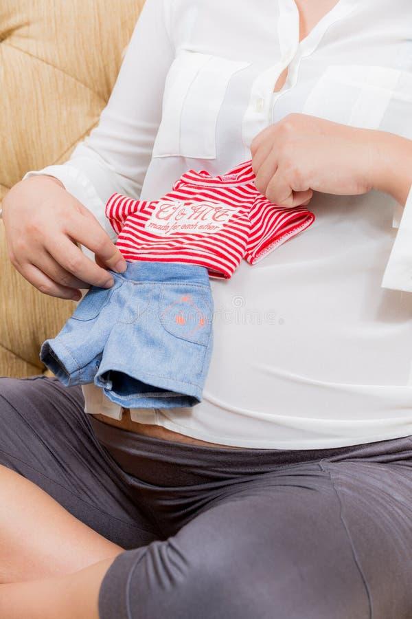 年轻人孕妇戏剧婴孩的衣服在有她的男孩的手上 图库摄影