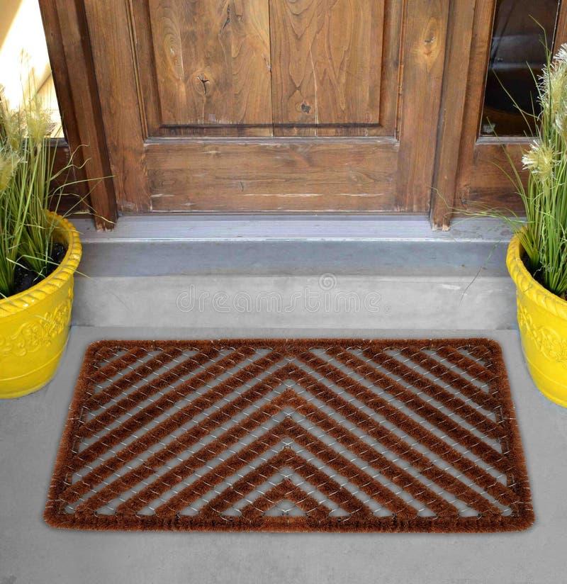 人字形室外/室内粗硬纤维刮板门前的擦鞋棕垫有黄色花和叶子的家外 库存照片