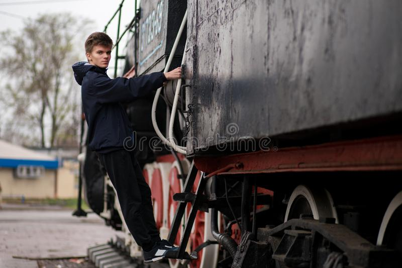 人学生画象火车站平台的在老火车附近的 r 免版税图库摄影