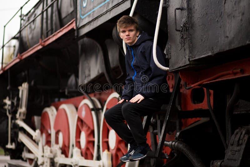 人学生画象火车站平台的在老火车附近的 r 图库摄影