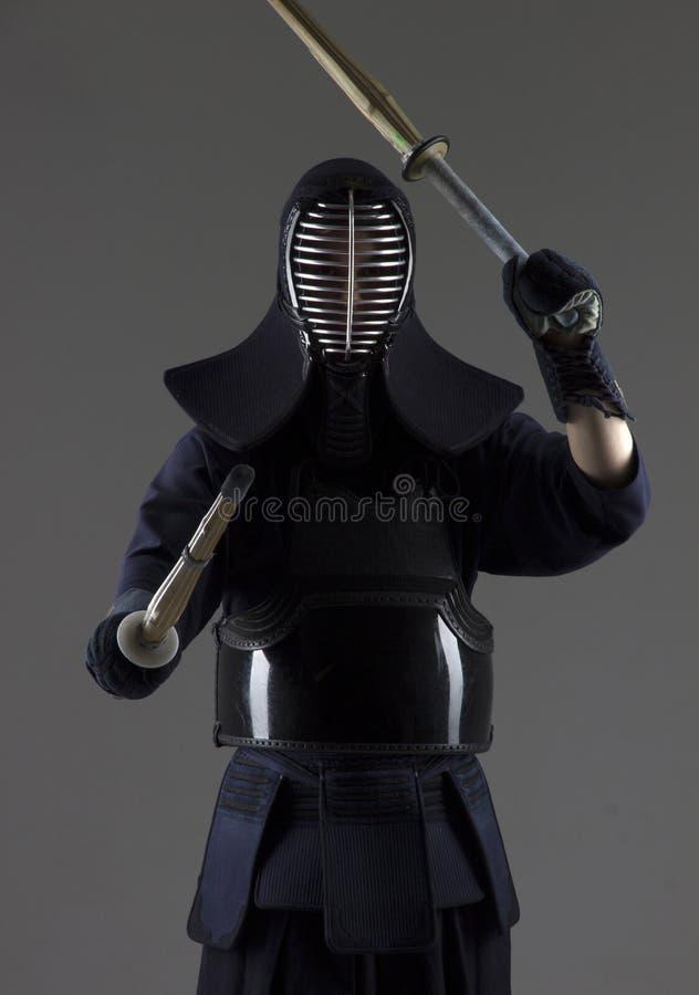 人实践在传统装甲的kendo 摇摆与两把竹剑的他 图库摄影
