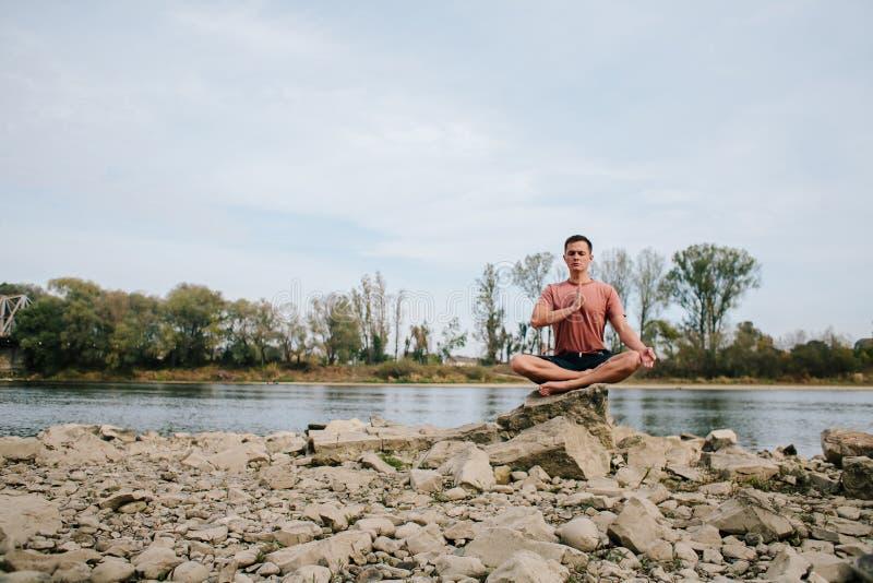 人实践在河岸的瑜伽 免版税库存照片