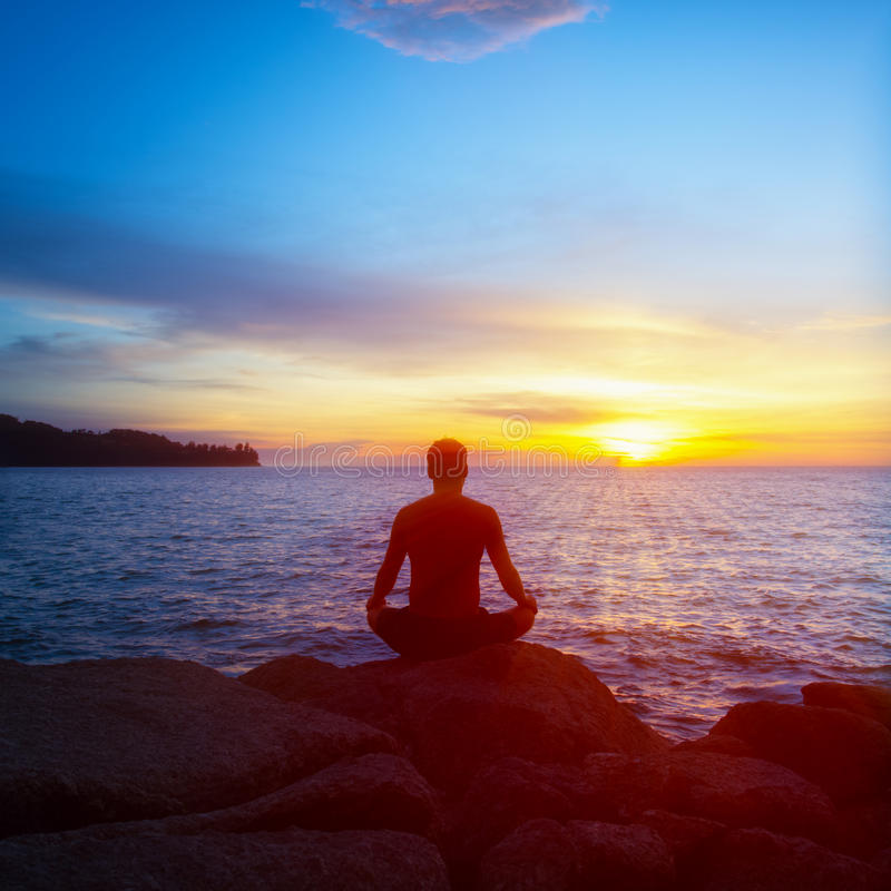 年轻人实践在海滩的瑜伽在日落 库存图片