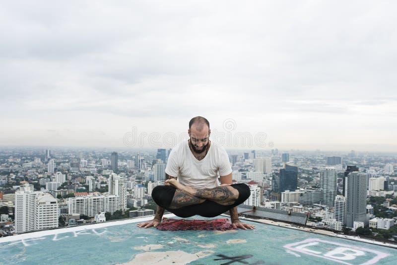 人实践瑜伽屋顶概念 图库摄影