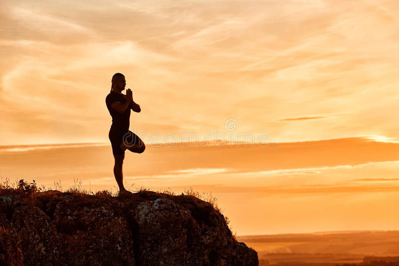 人实践的瑜伽的剪影在小山的反对美好的日落 库存照片