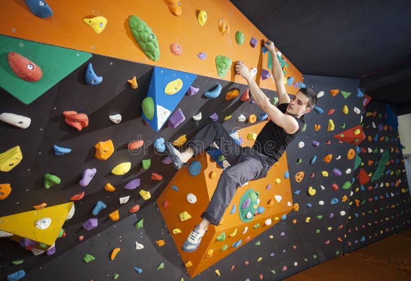 人实践的bouldering在室内上升的健身房 库存照片
