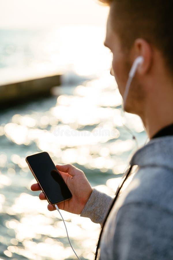 人室外照片使用手机的,站立在海附近 免版税库存照片