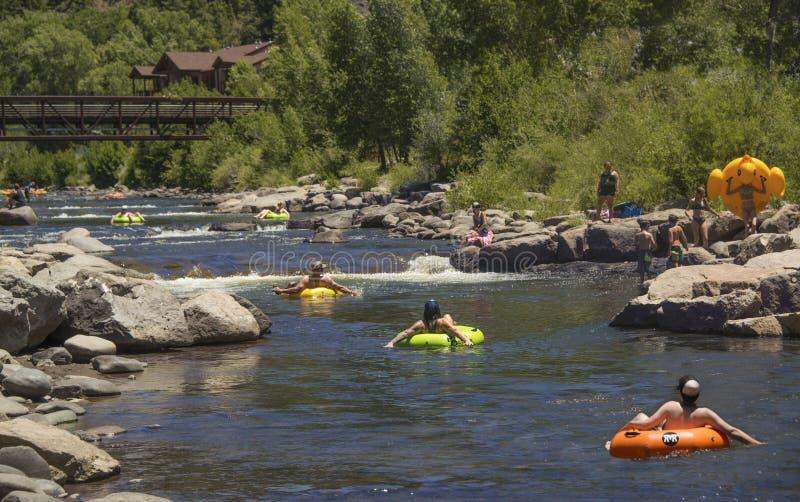 人家庭获得冷却漂浮的乐趣在可膨胀的管在热的夏日击倒圣胡安河在帕戈萨斯普林斯 免版税库存照片