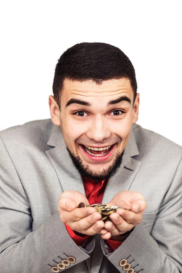 人对金钱满意 年轻快乐的有胡子的人在他的手上的拿着硬币 库存图片