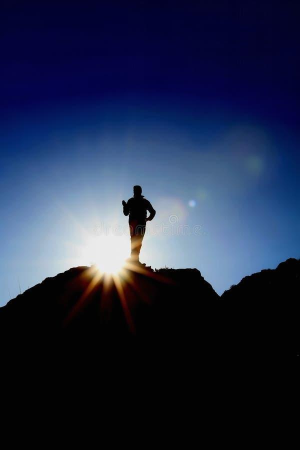 人小山上面太阳剪影 免版税图库摄影