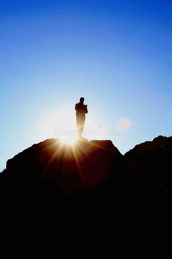人小山上面太阳剪影 图库摄影