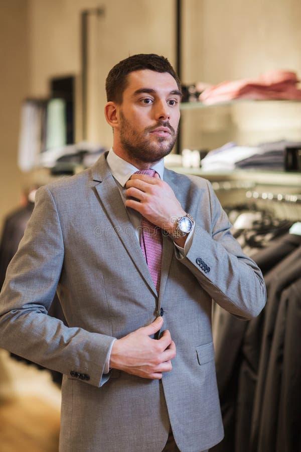 年轻人尝试的衣服在服装店 免版税库存图片