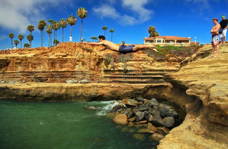 年轻人峭壁潜水到水,日落峭壁,洛马角,圣地亚哥,加利福尼亚里 免版税图库摄影