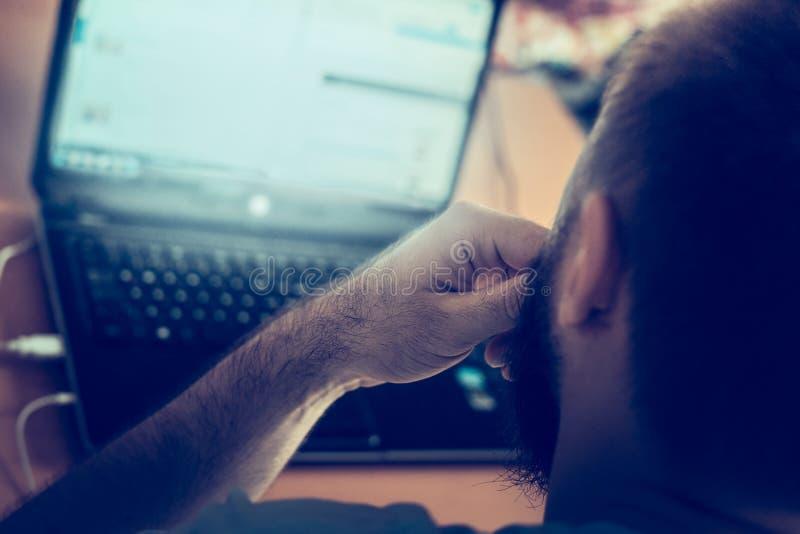 年轻人工作在计算机的,家庭办公室,被弄脏的背景 免版税库存图片