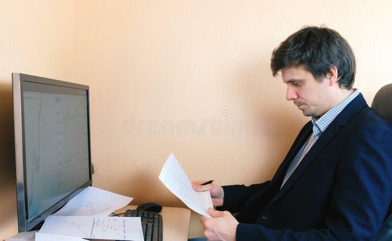 人工作在计算机 扫描在纸的图表 免版税库存图片