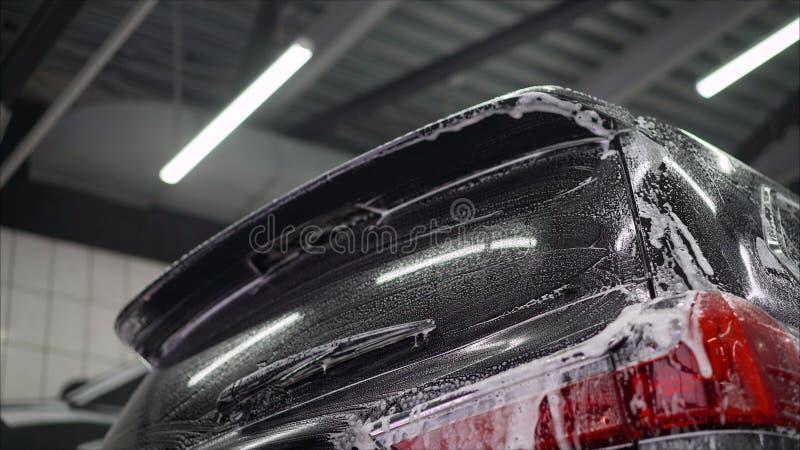 人工作者洗涤的汽车的在洗车的合金轮子 洗车洗涤汽车在洗车 免版税图库摄影