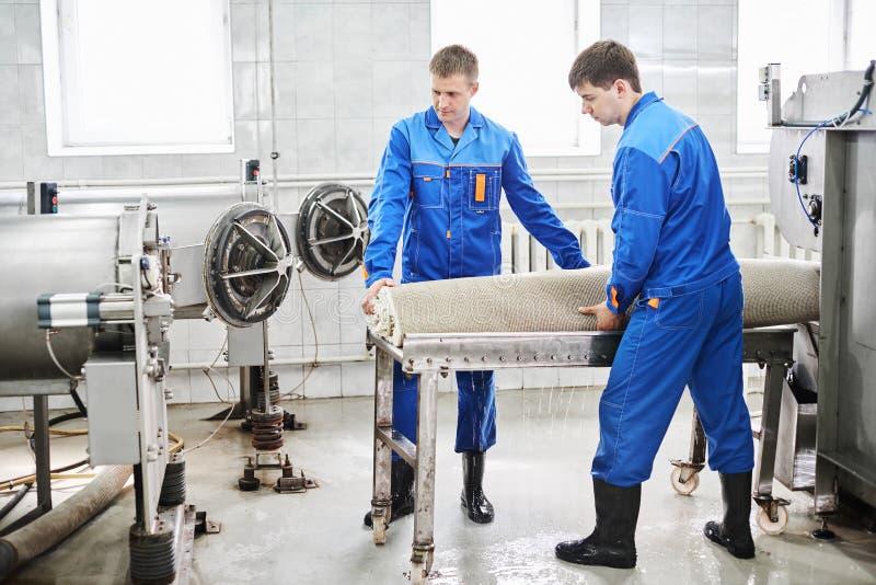 人工作者清洗从一台自动洗衣机得到地毯并且运载它在干衣机 免版税库存图片