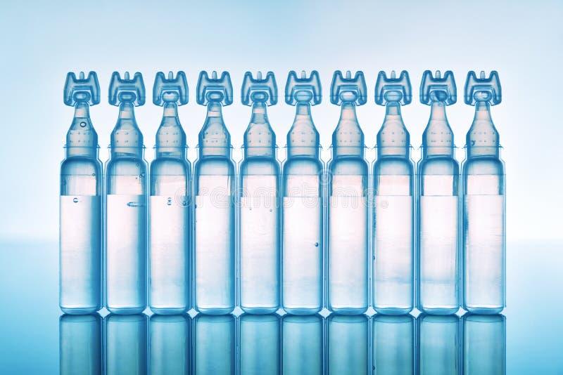 人工眼泪在塑料吸移管蓝色背景前面的眼药水 图库摄影