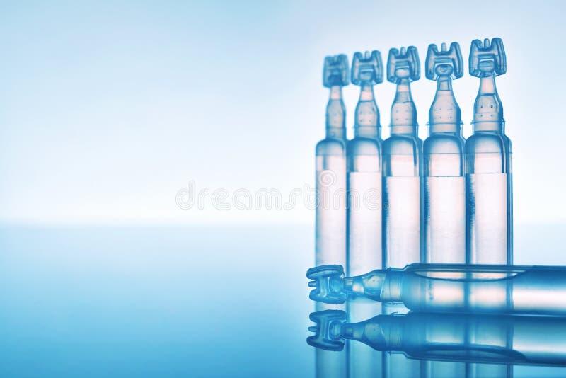 人工眼泪在塑料吸移管蓝色背景构成的眼药水 库存图片