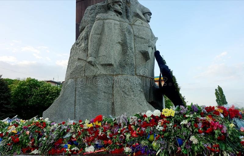 人带来的花给荣耀的纪念碑在法西斯主义, 5月9日的胜利天 免版税库存图片
