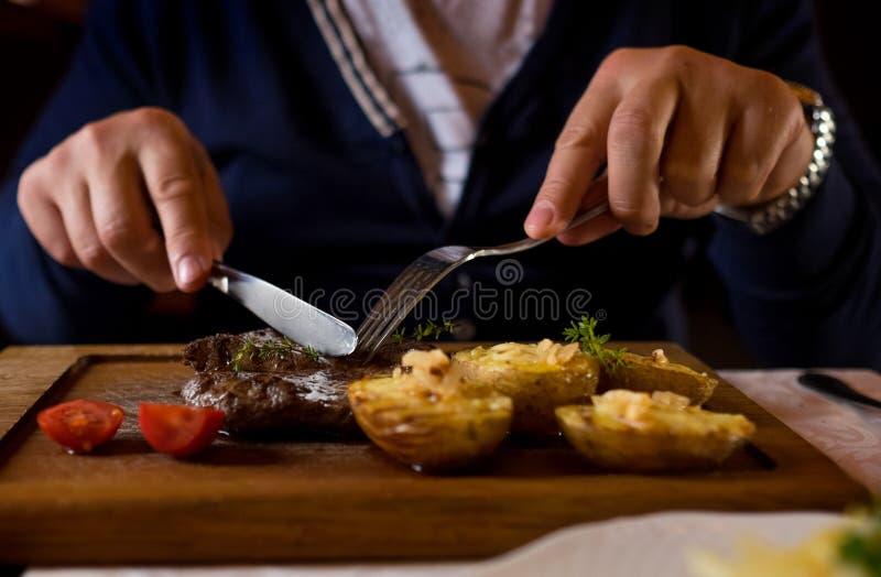 人开始吃媒介烤小牛肉牛排 递特写镜头视图 免版税库存图片
