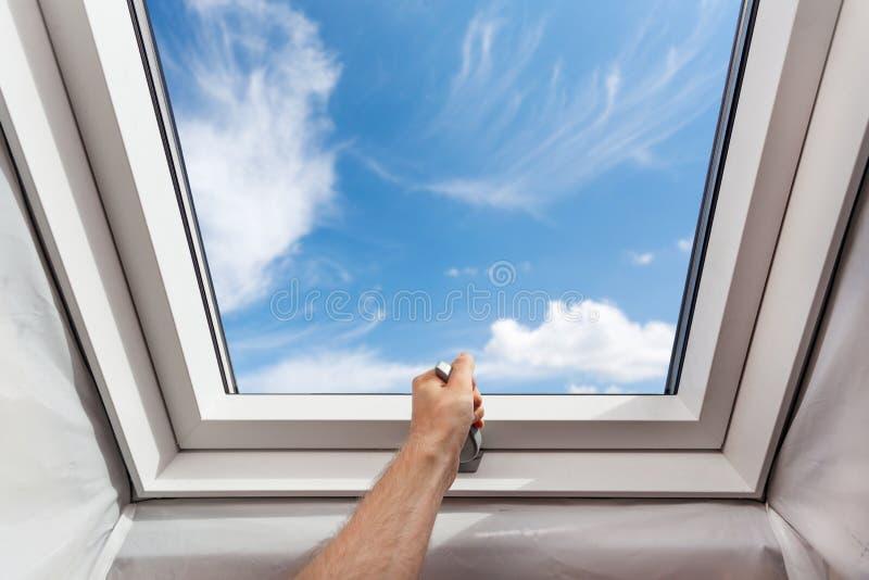 人开放新的天窗有双重斜坡屋顶的房屋的窗口在反对蓝天的一间顶楼屋子 免版税库存图片