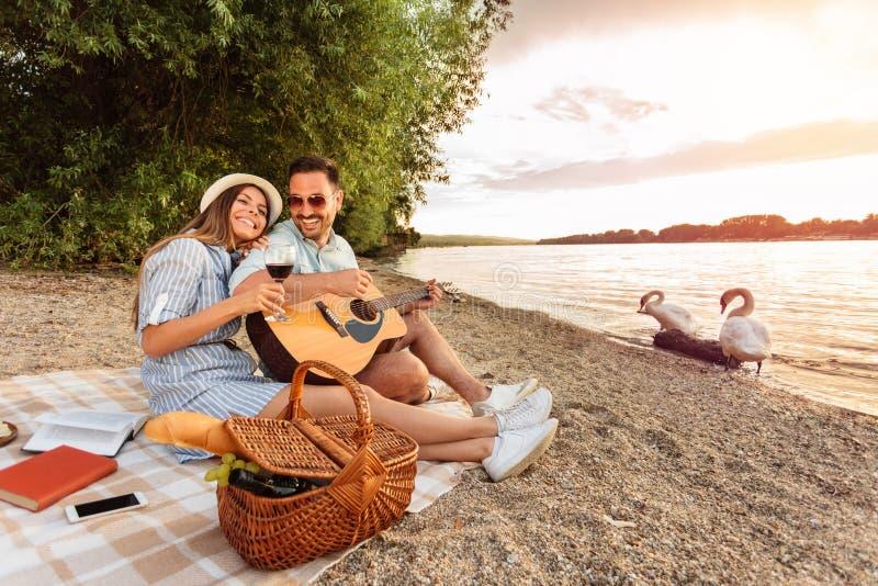 人弹吉他,并且他的女朋友休息她的在他的肩膀的头 在水的日落在背景中 免版税库存照片
