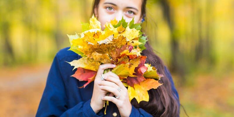 年轻人微笑的十几岁的女孩特写镜头拿着秋叶花束的 秋季 库存照片