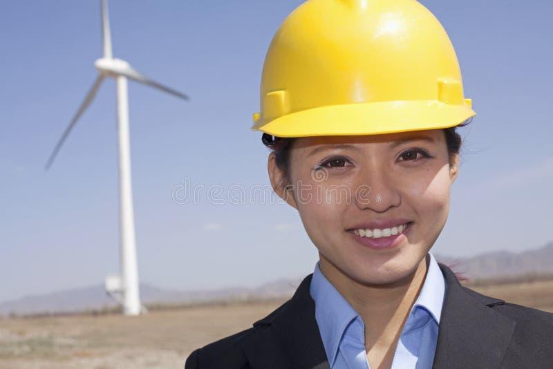 年轻人微笑的女性工程师画象检查在站点的风轮机 库存照片