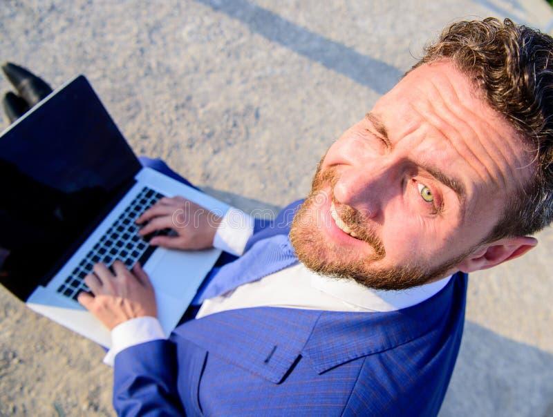 人微笑的快乐的面孔与膝上型计算机关闭一起使用 商人正式衣服神色,当举行打开屏幕膝上型计算机时 免版税库存图片