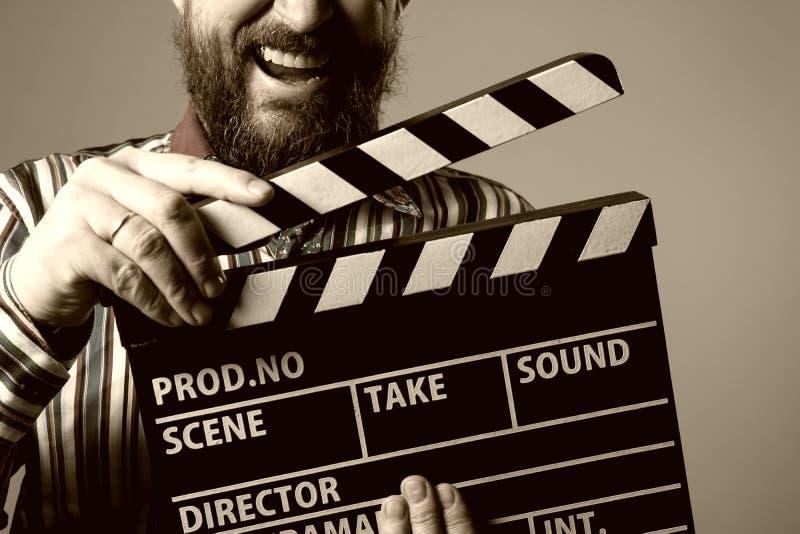 人微笑的clapperboard戏院的特写镜头 免版税库存照片