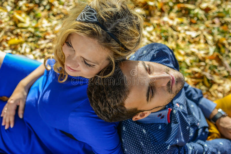 年轻人怀孕的夫妇坐黄色在公园离开 免版税库存照片