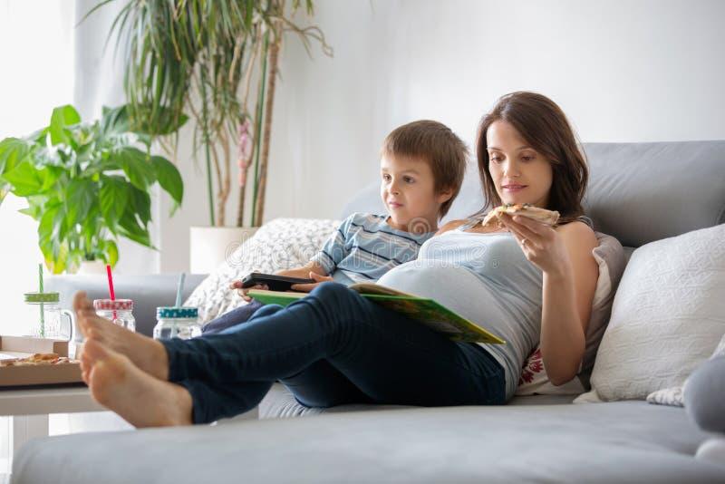 年轻人怀孕的母亲和她的男孩,在家吃鲜美薄饼, w 免版税图库摄影