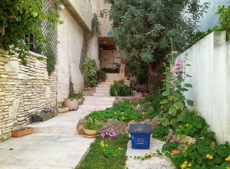 在右边,有绿色树和花圃有金莲花的 在庭院里是纸回收的小蓝色塑料盒图片