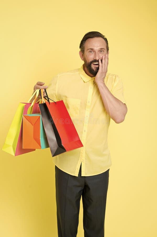 人成熟有胡子的快乐的面孔拿着购物带来 人得到了unexpectable礼物 E 免版税库存图片